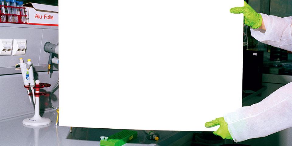 Weiße Pappe gehalten von grün behandschuhten Händen in einer Laborumgebung.
