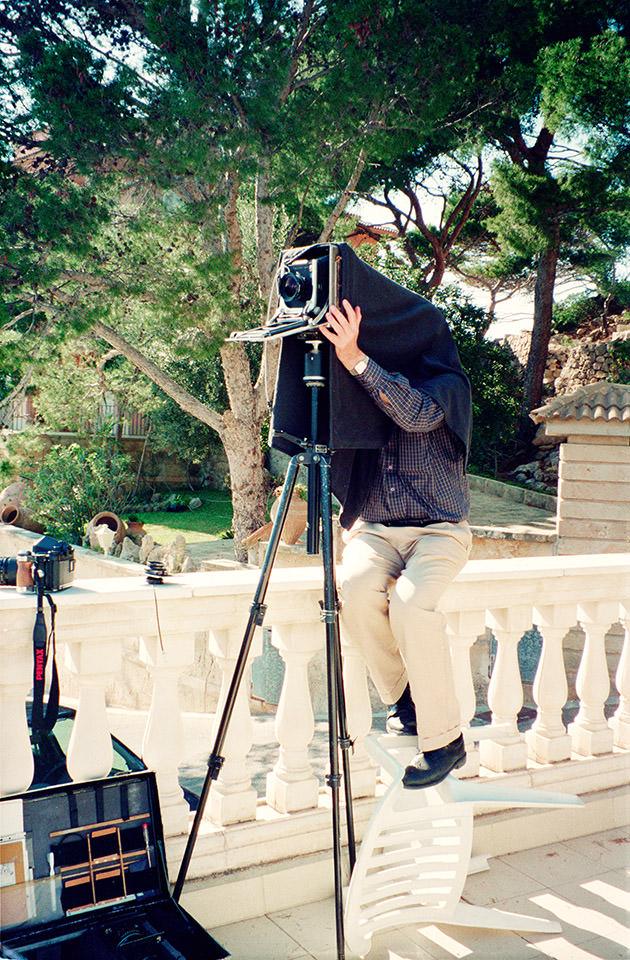 Ein Mann sitzt auf einer Brüstung an einer Großformatkamera in einer natürlichen Umgebung.