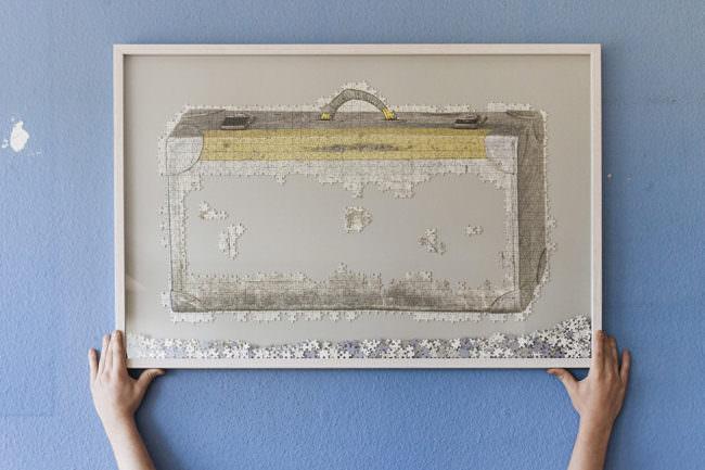 Angefangenes Puzzle eines Koffers in einem Bilderrahmen, der von zwei Händen gehalten wird.