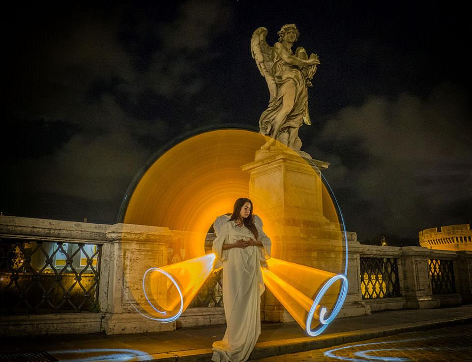 Eine Frau mit Lichtspur als Flügel vor einer Engelsstatue
