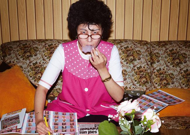Eine Frau in pinkem Hauskleid sitzt rauchend an einem Tisch und blickt über ihre Brille hinweg geradeaus.