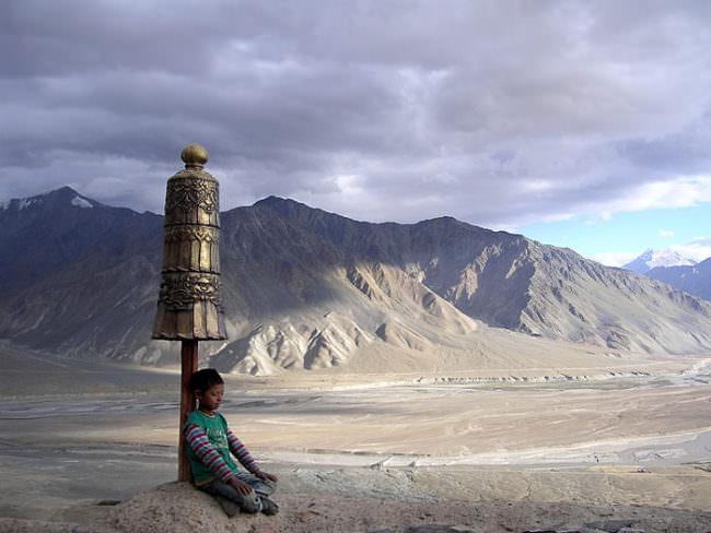 Ein Kind lehnt an einer Glocke vor einer Berglandschaft