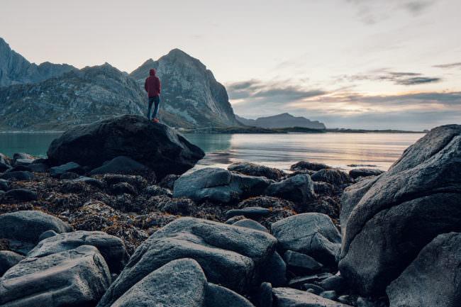 Eine Person steht auf einem Steinstrand und sieht aufs Meer