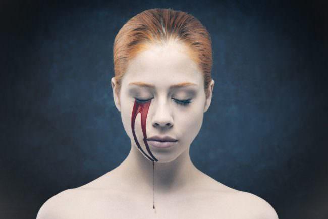 Eine Frau mit roter Farbe, die aus dem Auge läuft
