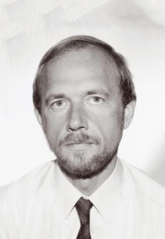 Farbloses Passfoto eines Mannes mit Bart und kurzen Haaren.