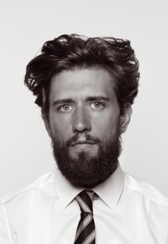 Farbloses Passfoto einen jungen Mannes mit dunklem, dichten Bart und mittellangen Haaren.