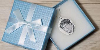 Fotogravurkette mit Portrait in einer blauen Geschenkverpackung.