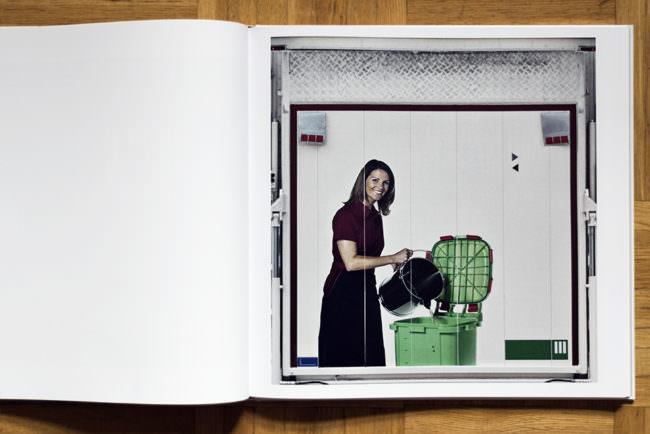 Aufgeschlagenes Buch mit Doppelseite wobei auf der rechten Seite die Rückseite eines LKW abgebildet ist ohne Text mit einer weiblichen Figur darauf.