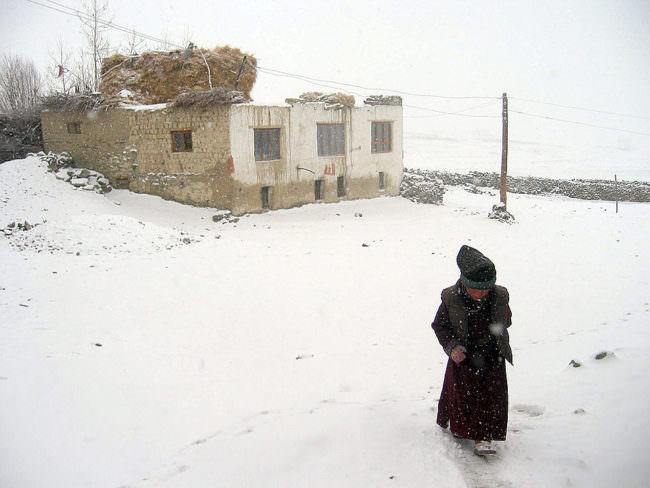 Eine Person im Schnee vor einem Haus