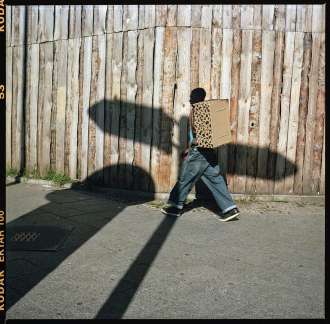 Ein Mann mit Karton auf dem rücken läuft die Straße entlang