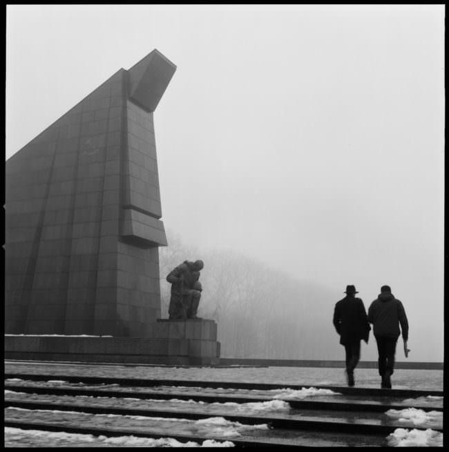 Zwei Spaziergänger an einem Denkmal