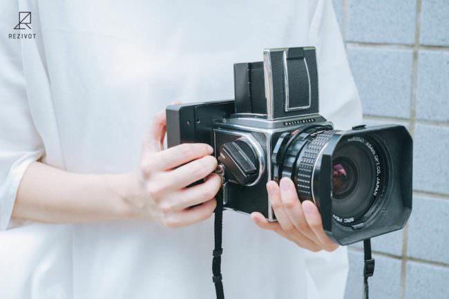 Eine Person hält eine Hasselblad mit einem Sofortbild-Rückteil in beiden Händen.