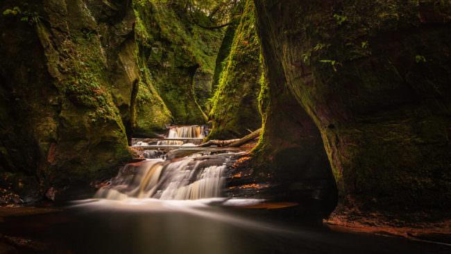 Kleiner Wasserfall zwischen bemoosten Felsen