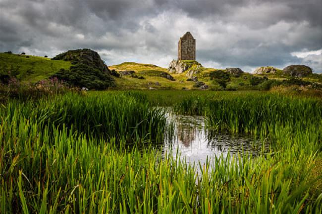 Teich im Vordergrund mit Burg im Hintergrund