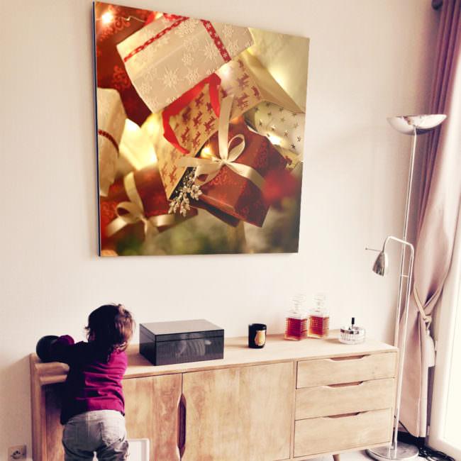 Wohnzimmeransicht mit Weihnachtsbild an der Wand und Kleinkind, das auf einen Stuhl klettert.