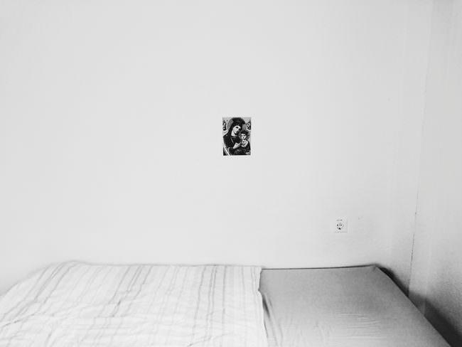 Ein Bett mit Ikonenbild an der Wand