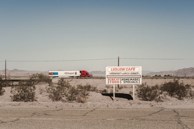 Ein Schild in der Wüste mit einem Truck in der Ferne