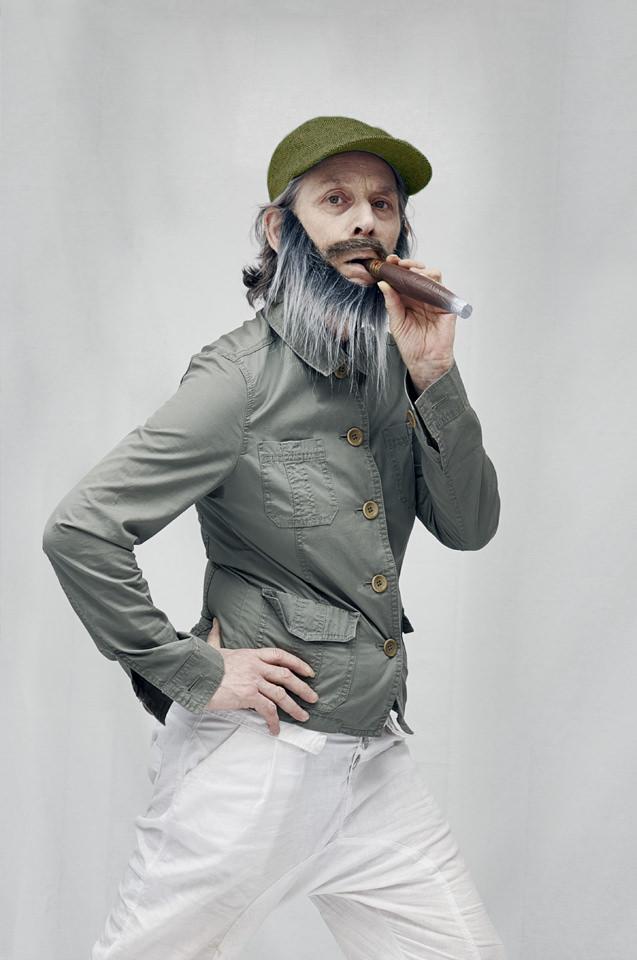 Person mit Theaterbart und Plastikzigarre gibt vor, im Gehen zu Rauchen. Dies geschieht vor einem Studiohintergrund.