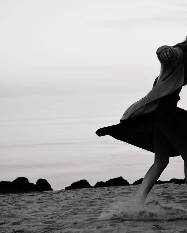 Eine Person tanzt im Sand