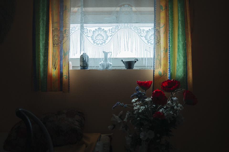 Blick auf ein Fenster, vor dem blühende Rosen zu sehen sind und fransige, weiße Vorhänge.