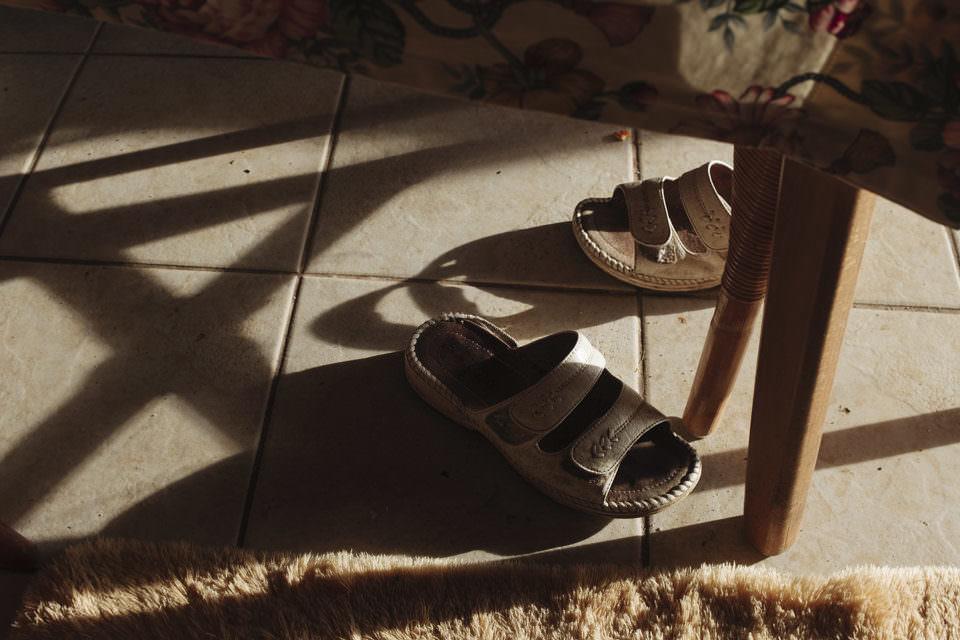 Blick auf gefliesten Boden, der von der Sonne beschienen ist mit Schattenwurf. Darauf liegen kreuz und quer zwei Paar Sandalenschuhe.