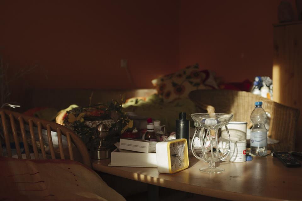 Übersicht über einen Tisch in einer sonnenbefleckten Ecke, auf dem Krimskrams liegt.