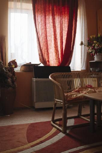 Innenraumaufnahme mit Fenster, vor dem weiße und rote Vorhänge hängen, davor ein Sofa.