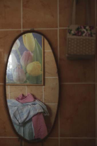 Ansicht eines ovalen Wandspiegels, in dem sich Stoffe und ein Tulpenbild spiegeln.