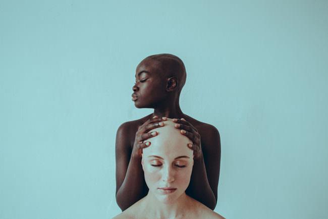 Zwei Frauen, eine hält die Hände beschützend auf den Kopf der anderen
