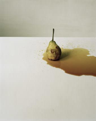 Eine Birne in einer braunen Flüssigkeitspfütze auf einem hellen Untergrund.