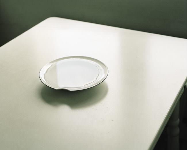 Ein Teller mit angeschlagener Kante, gefüllt mit Wasser auf einem hellen Untergrund.