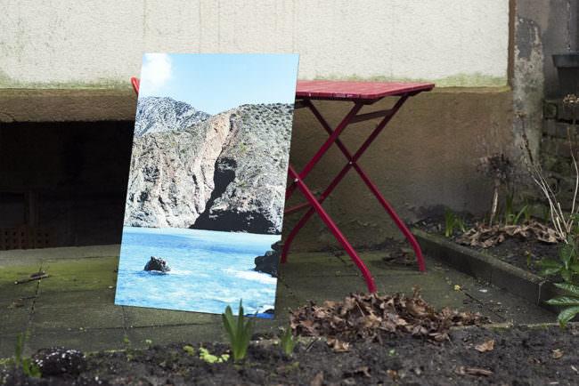 Bild einer Küstenmeerlandschaft auf Bildträger stehend im Außenraum angelehnt an einen roten Klapptisch.