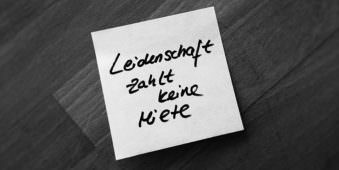 """Post it auf Holzgrund mit der Aufschrift """"Leidenschaft zahlt keine Miete""""."""