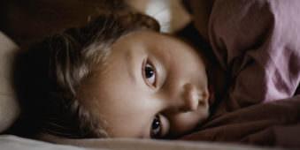 Gesicht eines liegenden Mädchens, welches einen direkt anblickt.