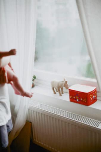 Fenster mit Fensterbank, auf dem ein Spieltier und eine rote Dose stehen. Am Rand unscharf der Körper eines Säuglings, der von jemandem gehalten wird.