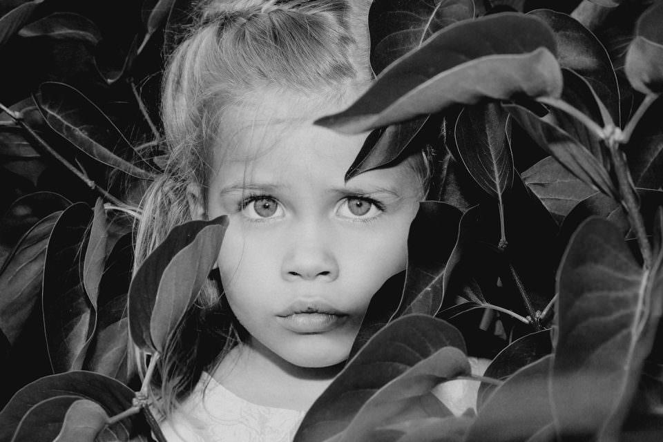 Mädchen zwischen Blättern eines Busches