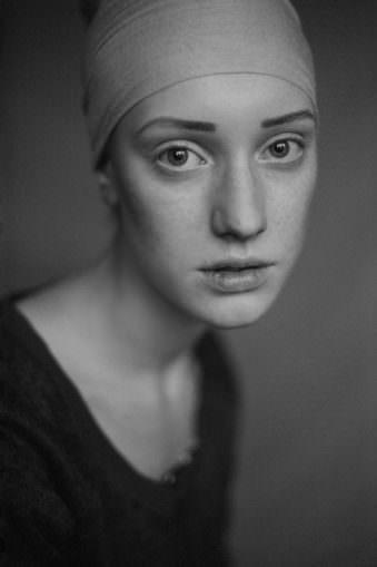 Junge Frau mit Kopftuch, die ernst und direkt schaut.