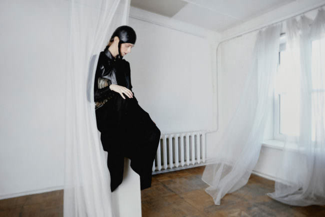 Frau in schwarzer Lederkleidung sitzt auf einem Sockel, umweht von weißen Vorhängen. Im Hintergrund ein weißer Raum mit einer Heizung.