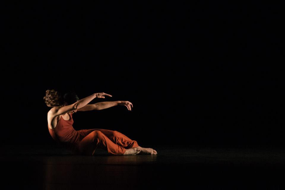 Person vor schwarzem Grund in orangem Gewand bei tänzerischer Bewegung, halb im Liegen.