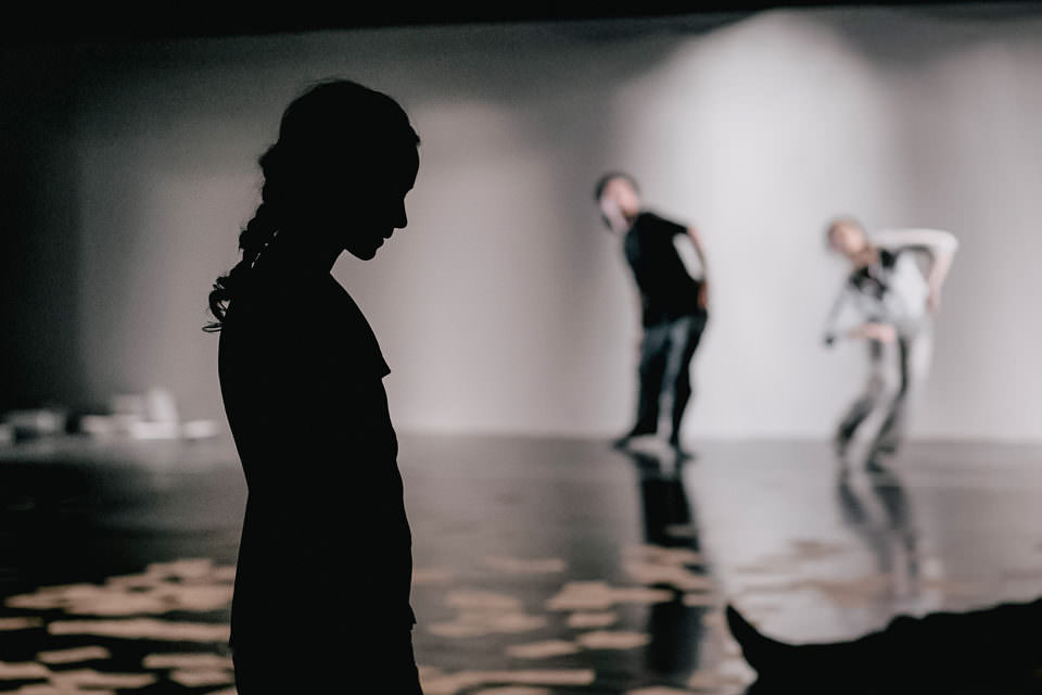 Drei Personen, schemenhaft erkennbar. Vorn eine dunkle Frauensilhoutte, dahinter versetzt zwei verschwommene Figuren.
