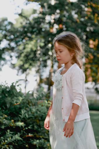 Ein Mädchen im Kleid steht mit geschlossenen Augen im Grünen.