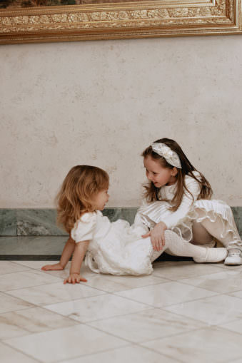 Zwei Mädchen in weißen Kleidchen spielen gemeinsam auf dem Boden.