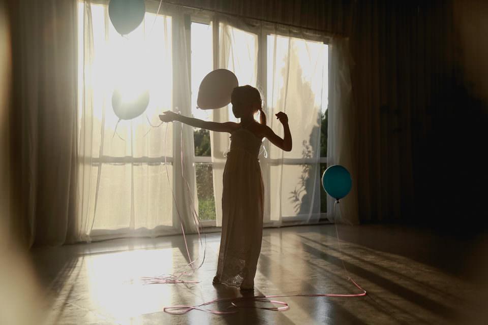 Mädchen als Umriss sichtbar im Kleid vor einem Fenster mit Luftballons, die in der Luft fliegen.