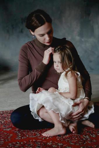 Frau sitzt auf dem Boden in braunem Oberteil und hat ein kleines Mädchen auf dem Schoß, das ein weißes Kleid trägt. Die Frau schaut herunter zu dem Mädchen.