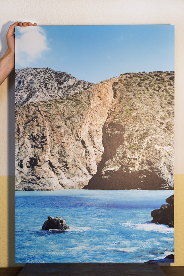 Bild einer Berglandschaft an einer Küste mit Wasser vor einer Wand. Gehalten von einer Hand.