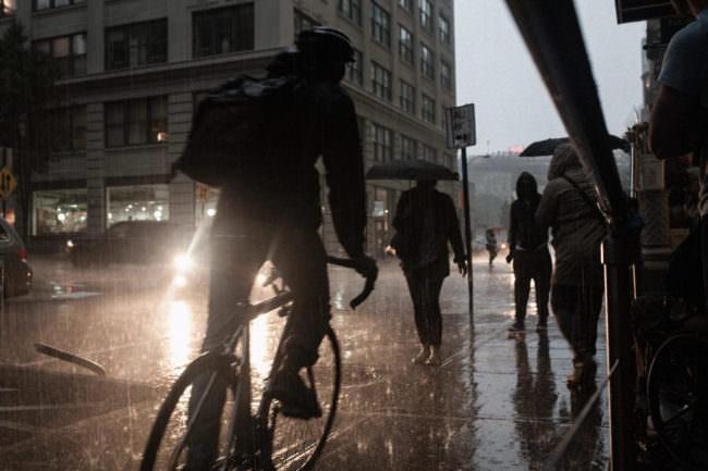 Straßenszene bei Regen mit einem ins Bild gefahrenen Radfahrer als Schattenfigur.