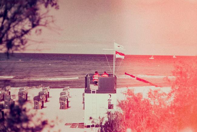 Übersicht über eine Strandszene mit Wasser im Hintergrund. Davor Strand mit Strandkörben und einer Seeretterstation. Von rechts kommt rotes Licht ins Bild.