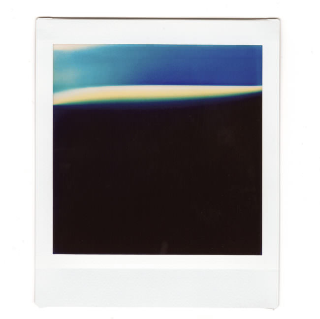 Ein abstraktes Polaroid mit blauer, weißer und schwarzer Fläche.