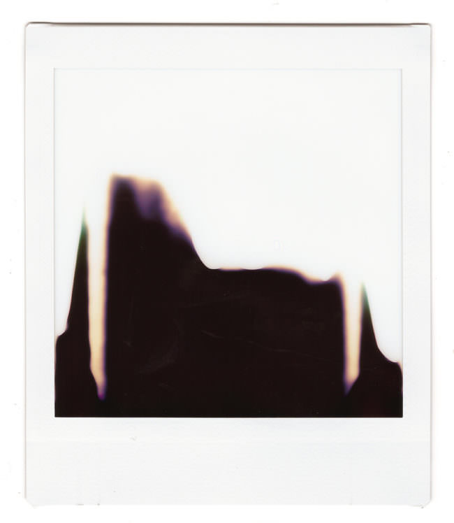 Ein abstraktes Polaroid mit heller Farbe oben die wie verlaufen zu sein scheint in eine dunklere Fläche unten.