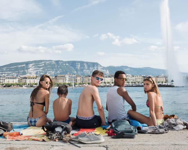Eine Gruppe Menschen sitzt an einem Steinufer